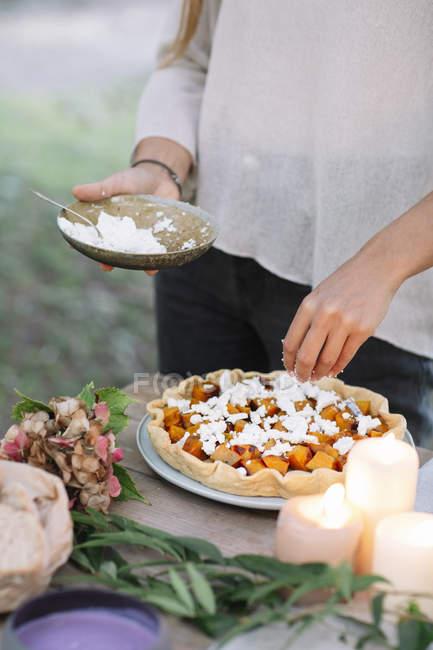 Primer plano de la mujer que prepara una cena romántica a la luz de las velas al aire libre - foto de stock