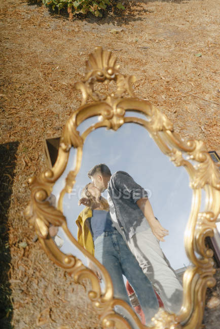 Affectionate young couple kissing reflected in vintage mirror — Stock Photo