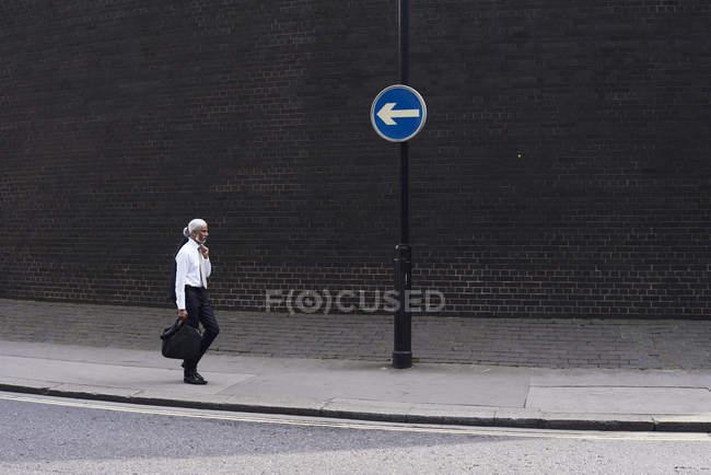 Элегантный старший бизнесмен с багажом, идущим по тротуару в противоположном направлении — стоковое фото