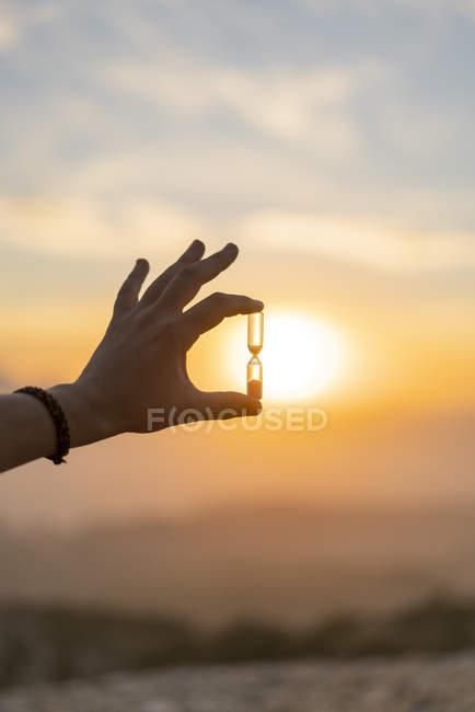 Крупный план мужской руки, держащей песочные часы на закате — стоковое фото