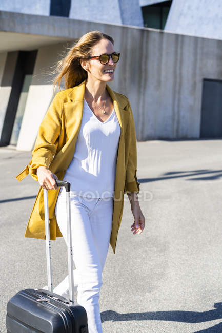 Smiling woman with suitcase in the city on the go — Stock Photo