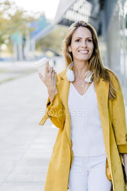 Retrato da mulher de sorriso com café takeaway — Fotografia de Stock