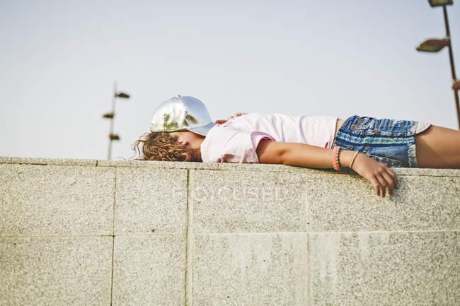 Fille se trouvant sur le mur, chapeau de base-ball sur la tête, visage obscurci — Photo de stock