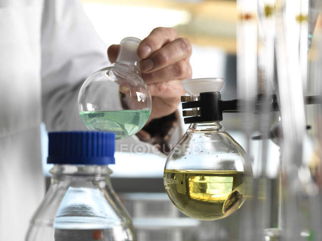 Scientist holding flask during an experiment in the laboratory — Stock Photo
