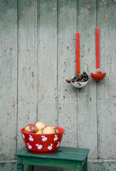 Decoração, tigela de esmalte com maçãs e peras, uvas azuis e nozes em conchas de sopa — Fotografia de Stock