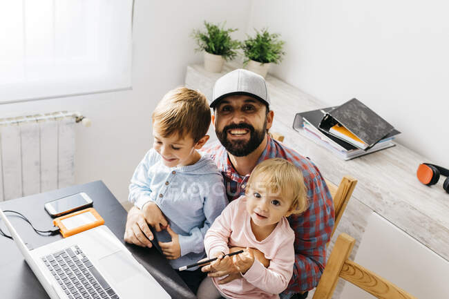 Father working at home, using laptop with his children on his lap — Stock Photo