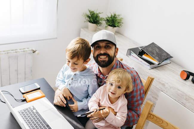 Vater arbeitet zu Hause, Laptop mit Kindern auf dem Schoß — Stockfoto