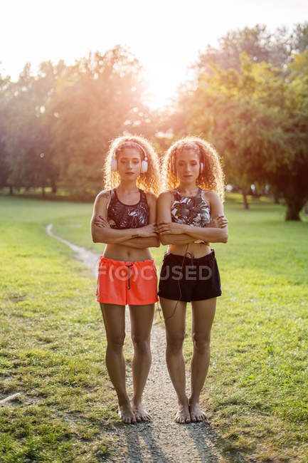 Portrait of twin sisters standing side by side in a park and listening music with headphones — Stock Photo