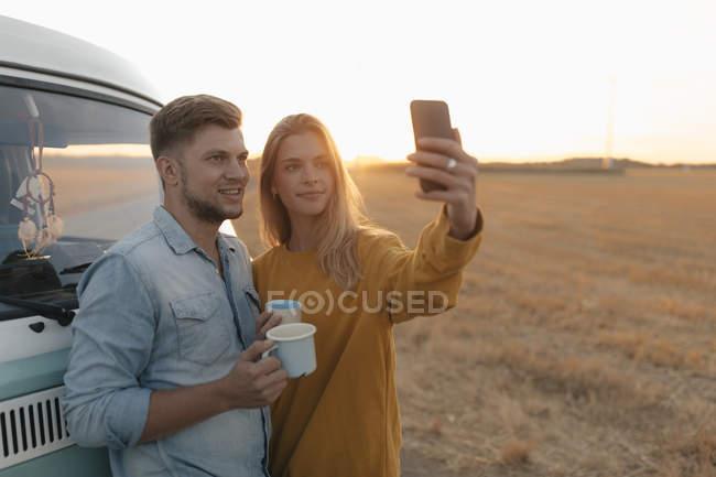 Молодая пара делает селфи в кемпере в сельской местности на закате — стоковое фото