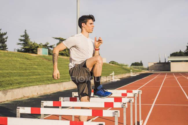 Спортсмен делает упражнения по разминке на тартановой трассе для забега на препятствиях — стоковое фото