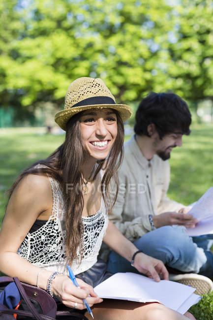 Портрет щасливих молодих студентів, які сидять у парку — стокове фото