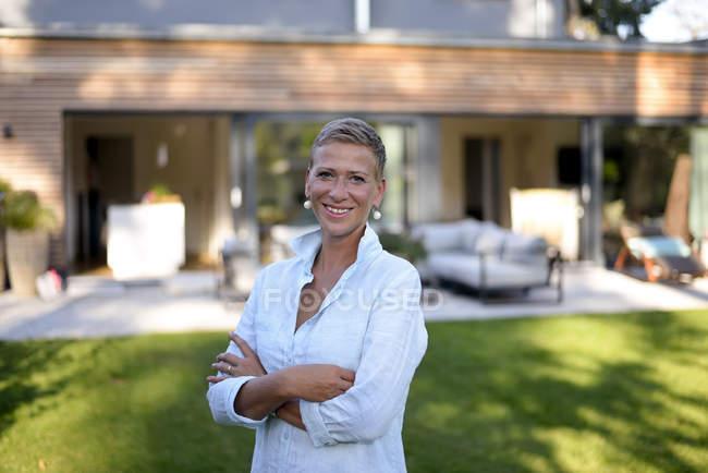 Портрет усміхненої жінки, що стоїть у саду свого будинку. — стокове фото