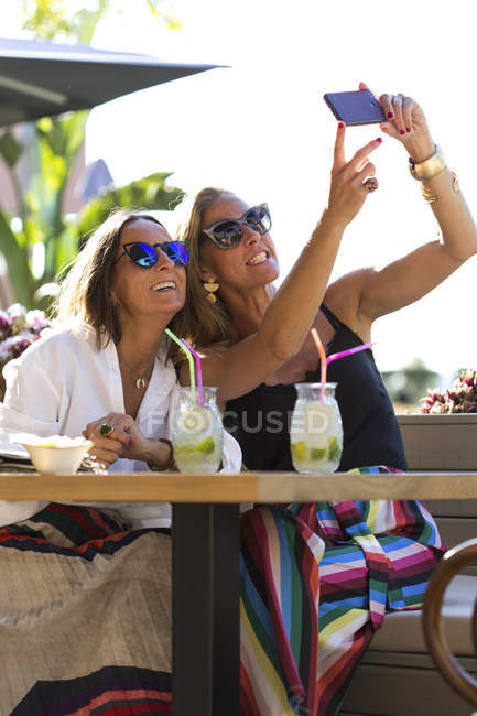 Happy girlfriends sitting outdoors with cocktail glasses taking a selfie — Stock Photo