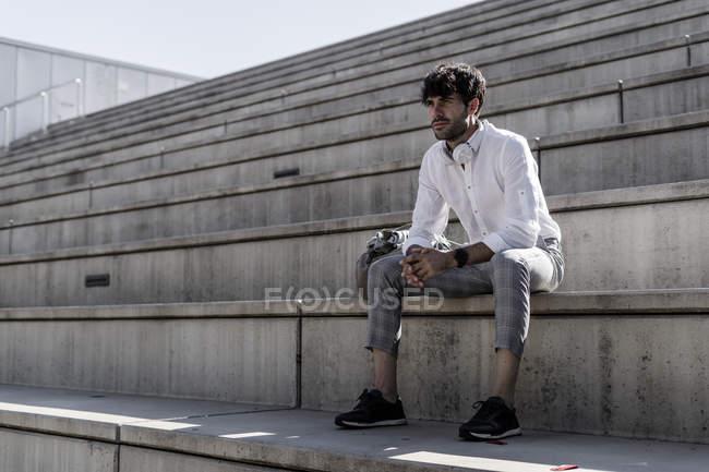 Jovem elegante com fones de ouvido sentado em escadas ao ar livre — Fotografia de Stock