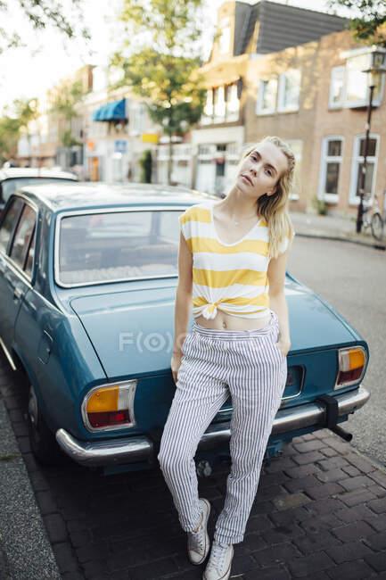 Портрет молодой женщины, стоящей перед винтажным автомобилем — стоковое фото