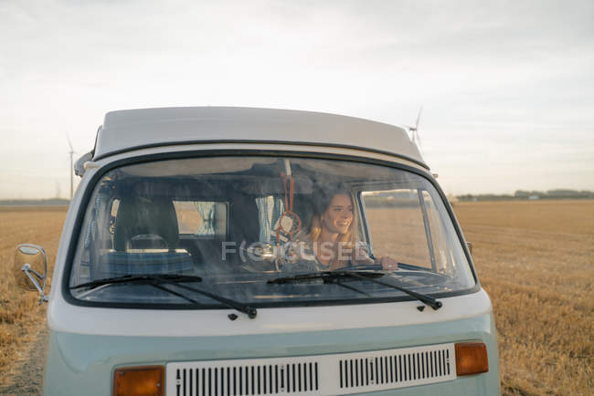 Happy young woman driving camper van in rural landscape — стокове фото