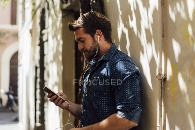 Man using earphones and smartphone outdoors — Stock Photo
