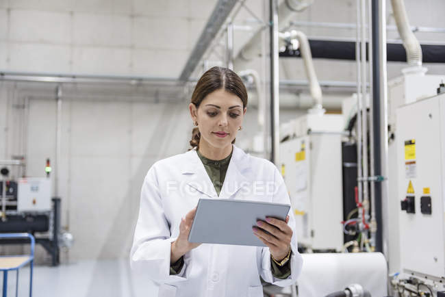 Woman checking manufacturing machines in high tech company, using digital tablet — Stock Photo