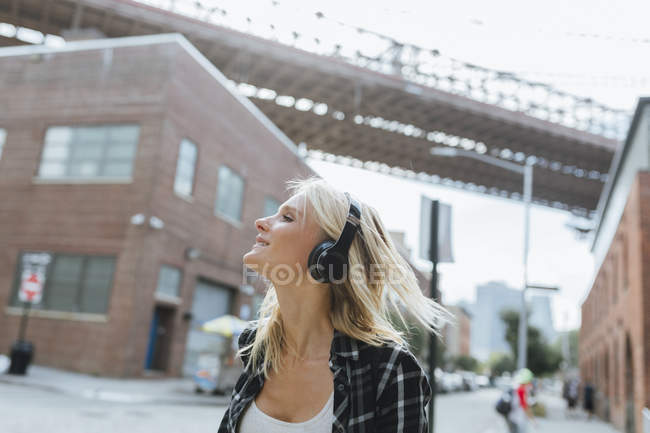 USA, New York City, Brooklyn, happy young woman listening to music with headphones in the city — Stock Photo