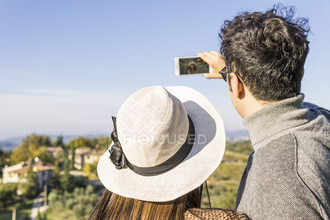 Italy, Tuscany, Siena, young couple taking a selfie at a winery — Stock Photo