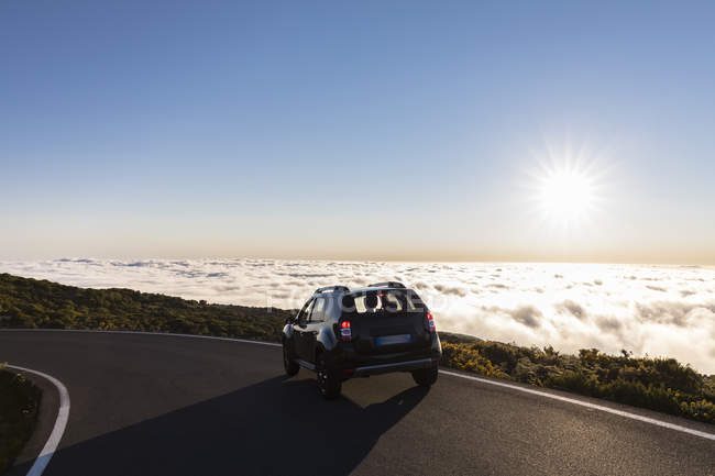 Reunion, Reunion National Park, car on the road to Maido viewpoint, sea of clouds and sunlight — Fotografia de Stock