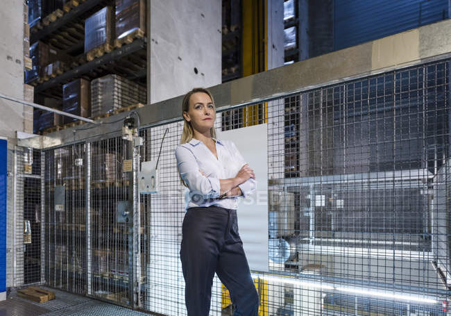 Blond woman in high rack warehouse — Stock Photo