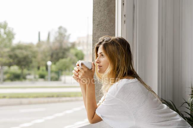 Giovane donna in piedi alla finestra e in possesso di una tazza di caffè — Foto stock