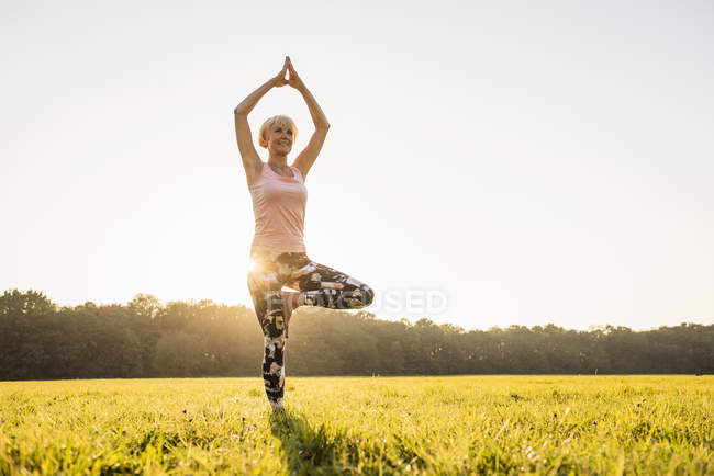 Senior woman doing yoga on rural meadow at sunset — Stock Photo