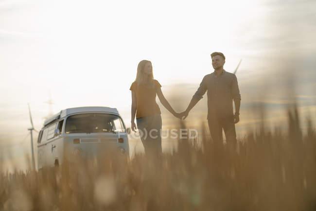 Молода пара рука об руку в автофургони Ван в сільській місцевості на заході сонця — стокове фото