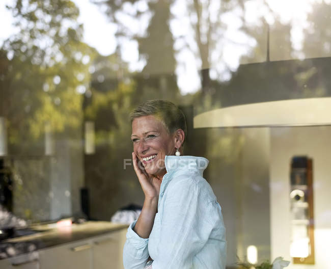 Portrait of laughing woman looking out of window — Stockfoto