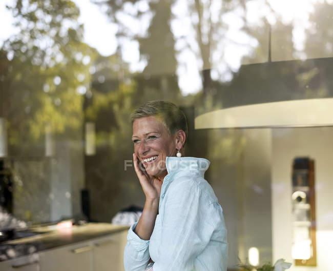 Porträt einer lachenden Frau, die aus dem Fenster schaut — Stockfoto