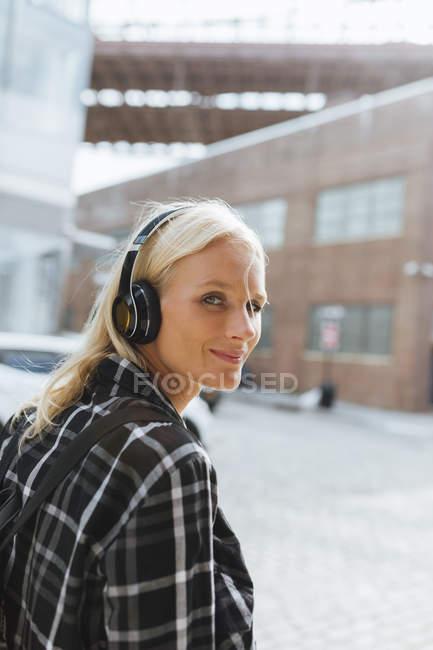 США, Нью-Йорк, Бруклин, улыбающаяся молодая женщина слушает музыку в наушниках в городе — стоковое фото