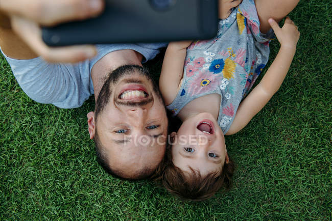 Happy father and daughter taking a selfie with cellphone on green grass — Stock Photo