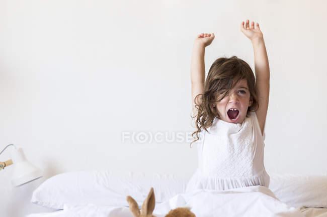 Bambina seduta sul letto allungandosi — Foto stock