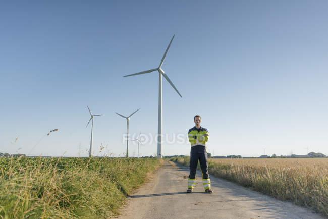 Инженер, стоящий на полевой дорожке на ветровой электростанции — стоковое фото