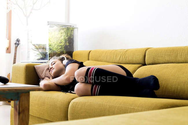 Girl lying on the couch at home listening music with headphones and smartphone — Stock Photo