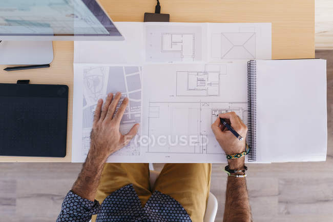 Close-up of architect working at home on floor plan — Stock Photo