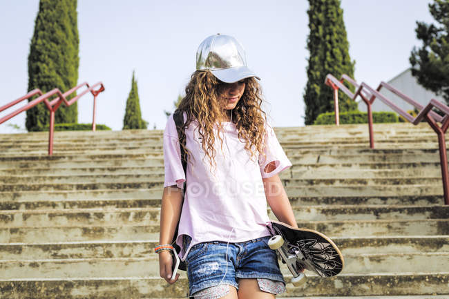 Girl with skateboard on steps — Stock Photo
