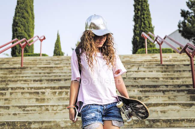 Menina com skate em passos — Fotografia de Stock