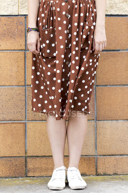 Young woman wearing brown dress with white polka dots, partial view — Stock Photo