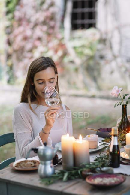Женщина пробует бокал вина за садовым столом — стоковое фото
