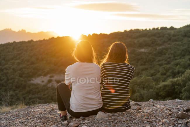 Amici che guardano il tramonto da una montagna — Foto stock