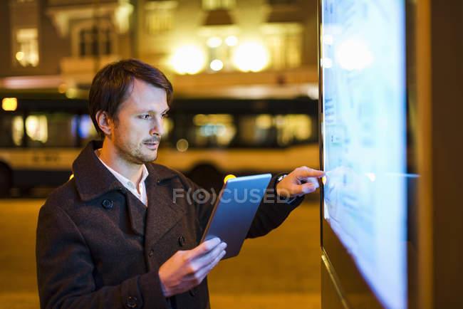 Empresário usando tablet digital à noite na cidade — Fotografia de Stock