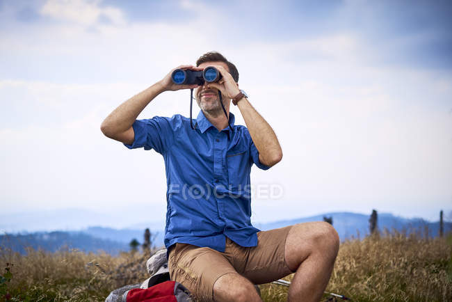 Man looking through binoculars during hiking trip — Stock Photo