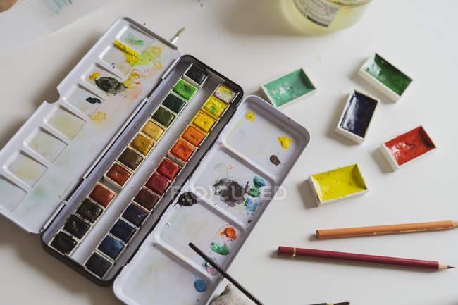 Acquerelli e matite colorate sulla scrivania — Foto stock