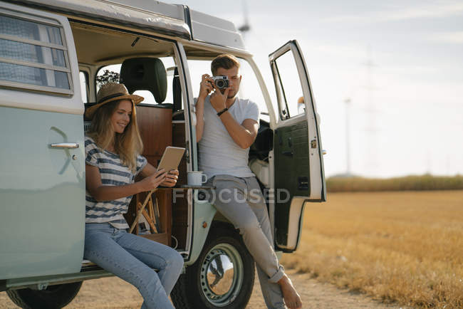 Young couple with tablet and camera at camper van in rural landscape — стокове фото