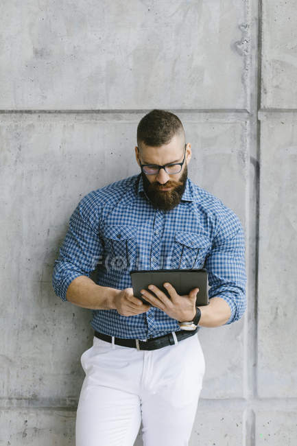 Bearded hipster businessman wearing glasses and plaid shirt, leaning against wall and using tablet — Stock Photo
