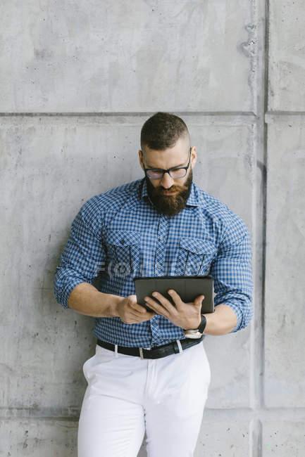 Uomo d'affari barbuto hipster indossa occhiali e camicia a quadri, appoggiata al muro e utilizzando tablet — Foto stock