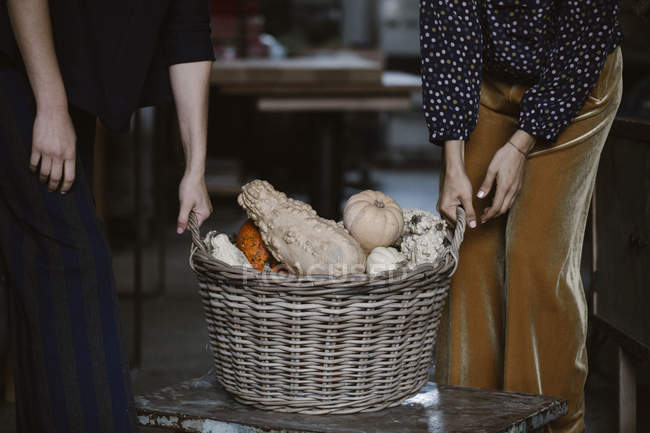 Two women with wickerbasket of decorative gourds, partial view — Stockfoto