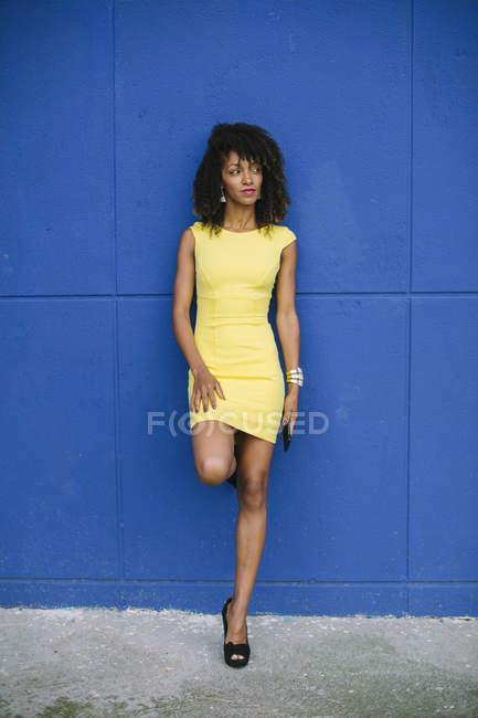 Ritratto di donna d'affari alla moda con cellulare appoggiato contro parete blu — Foto stock
